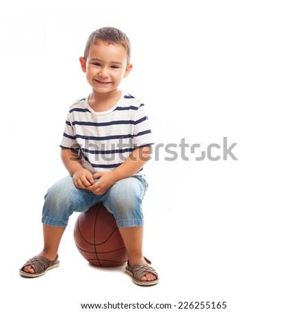 portrait of a little boy sitting on a basketball - stock photo