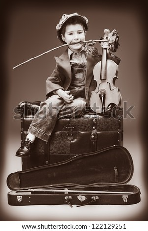 Portrait of a little boy sitting on a big old trunk with his violin and red rose. Retro style. - stock photo