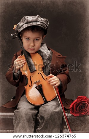 Portrait of a little boy sitting on a big old trunk with his violin. Retro style. - stock photo