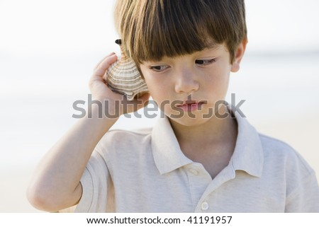 Portrait of a Little Boy Standing at The Beach Listening To A Shell