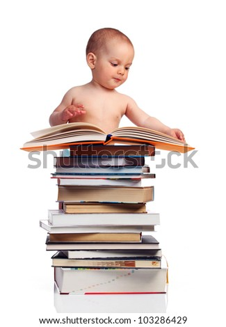 Portrait of a little boy standing behind a stack of books and turning pages of the book on the top, isolated over white