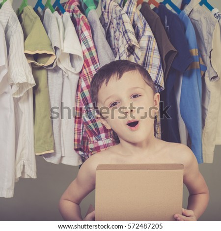 portrait of a little boy standing near a hanger with clothes at home at the day time