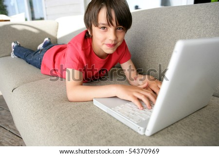 Portrait of a little boy stretched out on a sofa in front of a laptop computer