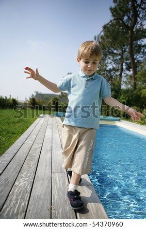 Portrait of a little boy walking beside a pool - stock photo