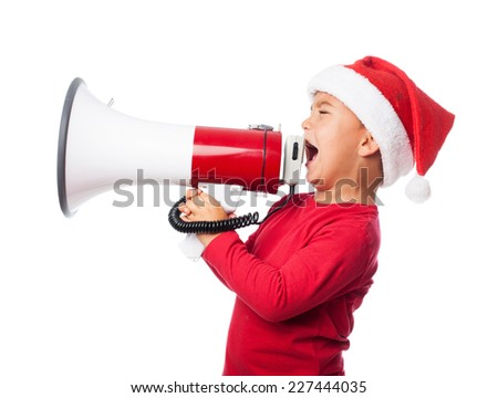 portrait of a little boy wearing a christmas hat and screaming by megaphone - stock photo