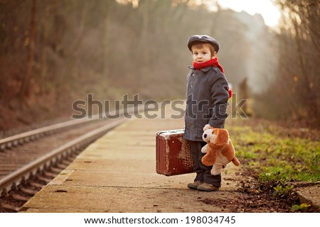 Portrait of a little boy with s suitcase and a teddy dog, waiting on a railway station  - stock photo