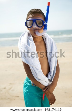 Portrait of a little boy with snorkel equipment by the beach - stock photo