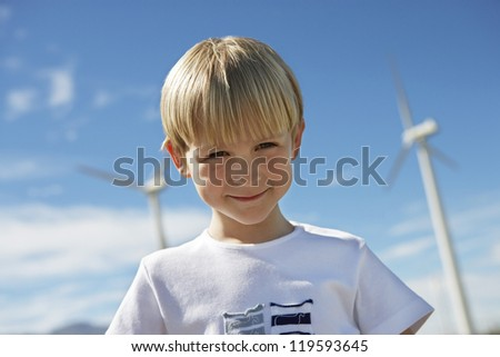 Portrait of a little boy with wind turbines in the background - stock photo