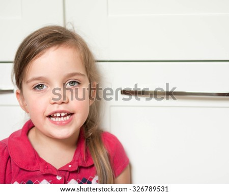 portrait of a little caucasian girl sitting in the kitchen and talking to her parent - stock photo