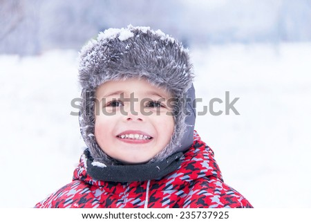 Portrait of a little cute boy on winter background. Happy child (kid) is enjoying view  of winter snow day. Smiling toddler is having fun.  Outdoor. Close up. - stock photo