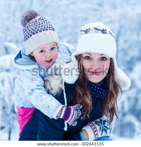 portrait of a little girl and her young beautiful mother in winter hat in snow forest at snowflakes background. outdoors winter leisure and lifestyle with kids on cold days - stock photo