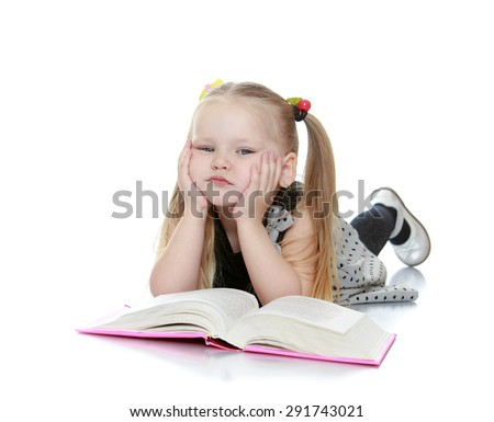 Portrait of a little girl blondes who reads a book while lying on the floor - isolated on white background - stock photo