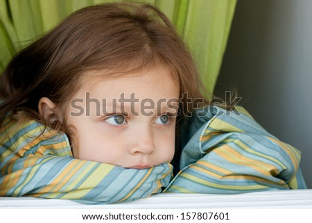 portrait of a little girl covered by blanket in the open window - stock photo
