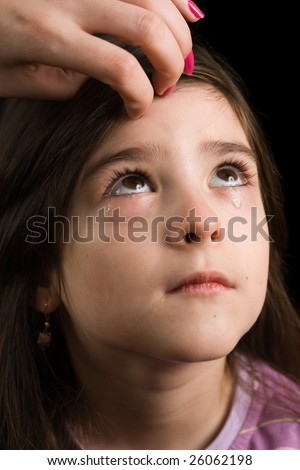 Portrait of a little girl crying, isolated on black background - stock photo