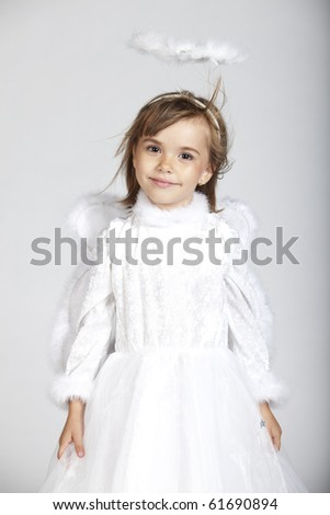 Portrait of a little girl dressed as an angel with white dress and halo, smiling, studio image
