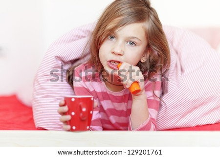 Portrait of a little girl eating healthy meal on the bed in her bedroom - stock photo