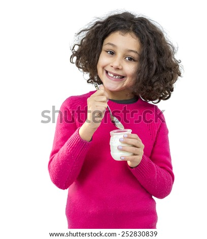 Portrait of a little girl eating yogurt isolated on white