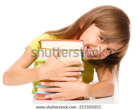 Portrait of a little girl embracing her books, isolated over white - stock photo