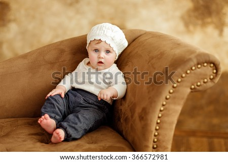 Portrait of a little girl eyed little girl in a white beret sitting on the couch on a brown background in studio - stock photo