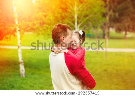 Portrait of a little girl hugging her father outside while having fun together. Happy daddy with daughter playing in summer sunny day. - stock photo