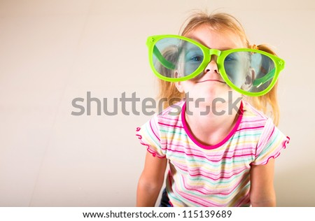 portrait of a little girl in big sunglasses - stock photo