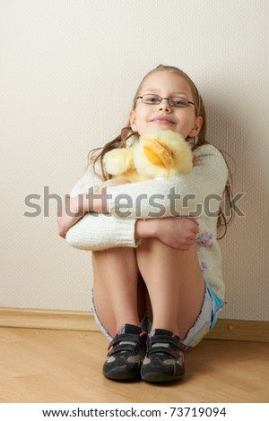 Portrait of a  little girl in eyeglasses with a toy, studio shot