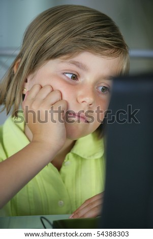 Portrait of a little girl in front a laptop computer - stock photo
