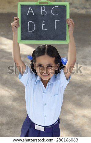 Portrait of a little girl in school uniform holding slate - stock photo