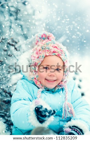 portrait of a little girl in winter clothes in snow forest at snowflakes background - stock photo