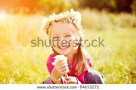 Portrait of a little girl in wreath of flowers - stock photo