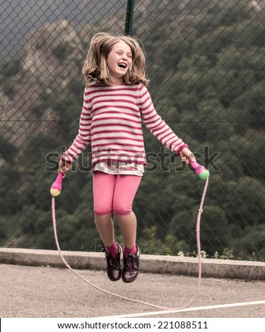 Portrait of a little girl jumping rope - stock photo