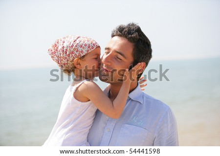 Portrait of a little girl kissing a man on the cheek