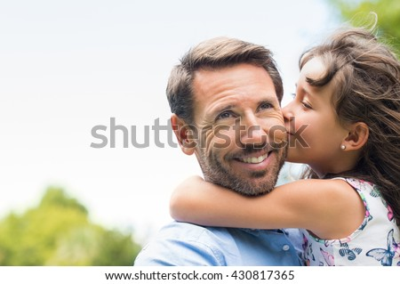 Portrait of a little girl kissing her dad on cheek. Pretty girl giving a kiss to her father outdoor. Loving child embrace and kissing her father. - stock photo