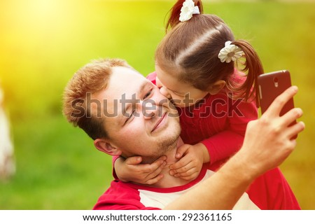 Portrait of a little girl kissing her father on cheek while taking selfie with phone. Close up face of happy parent with daughter outside. Little girl hugging neck of her daddy in summer day outdoors
