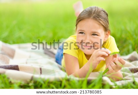 Portrait of a little girl laying on green grass, outdoor shoot - stock photo