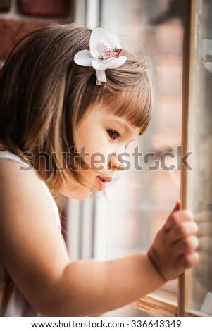 portrait of a little girl looking out the window - stock photo