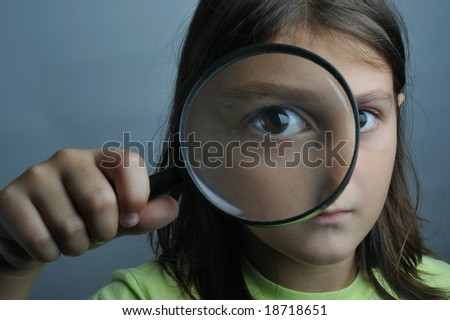 Portrait of a little girl looking through a magnifying glass