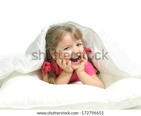 Portrait of a little girl lying in bed, gay, white background - stock photo