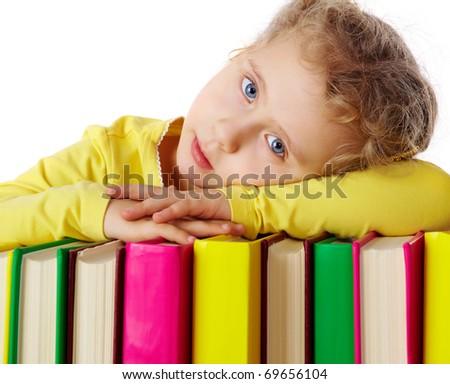 Portrait of a little girl lying on books - stock photo