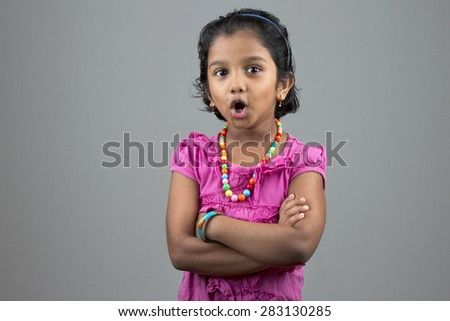 Portrait of a little girl of Indian origin with a surprised face - stock photo