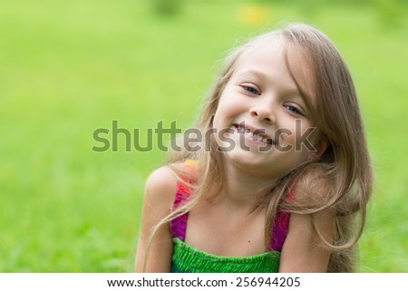 Portrait of a little girl on a green background. Girl seven years. - stock photo