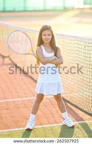 portrait of a little girl on the tennis court - stock photo