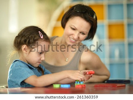 Portrait of a little girl painting with her mother - stock photo