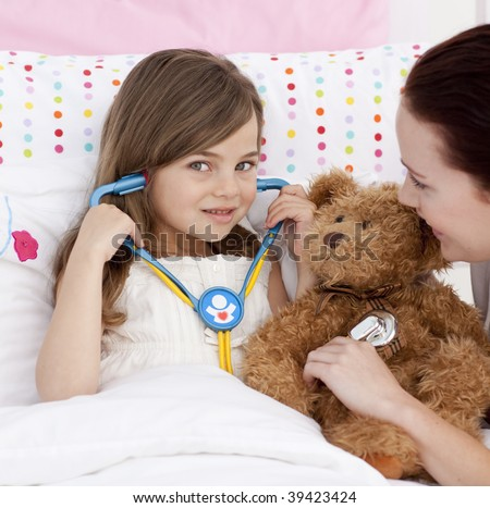 Portrait of a little girl playing with a stethoscope with her mother - stock photo