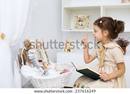 Portrait of a little girl reading book to her textile handmade princess dolls - stock photo