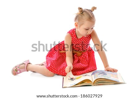 portrait of a little girl reading books, sitting on the floor  - stock photo