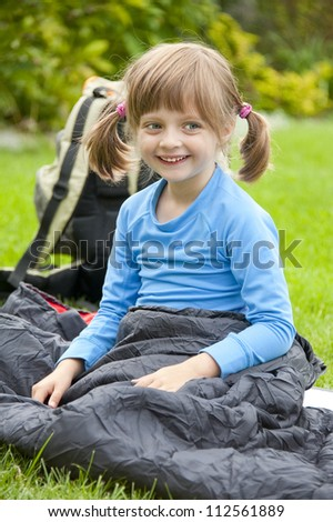 portrait of a little girl resting in a sleeping bag - camping concept - stock photo
