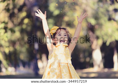 Portrait of a little girl running and playing in the park wearing a beautiful dress - stock photo