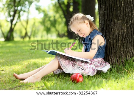 Portrait of a little girl sitting and reading on the grass in the park - stock photo