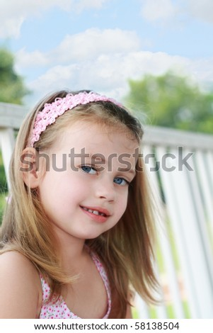 Portrait of a little girl sitting on a porch swings on a beautiful summer day. - stock photo